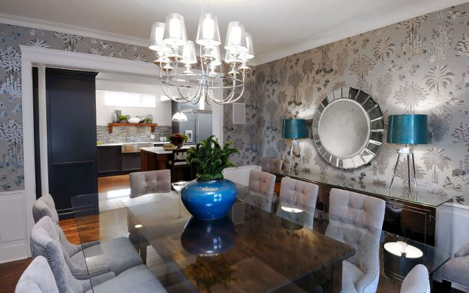 Modern Chandelier With Chandelier Shades And Glass Dining Table Plus Upholstered Dining Chairs Also Buffet Lamps On Sideboard With Wallpaper Plus Round Mirror In Transitional Dining Room