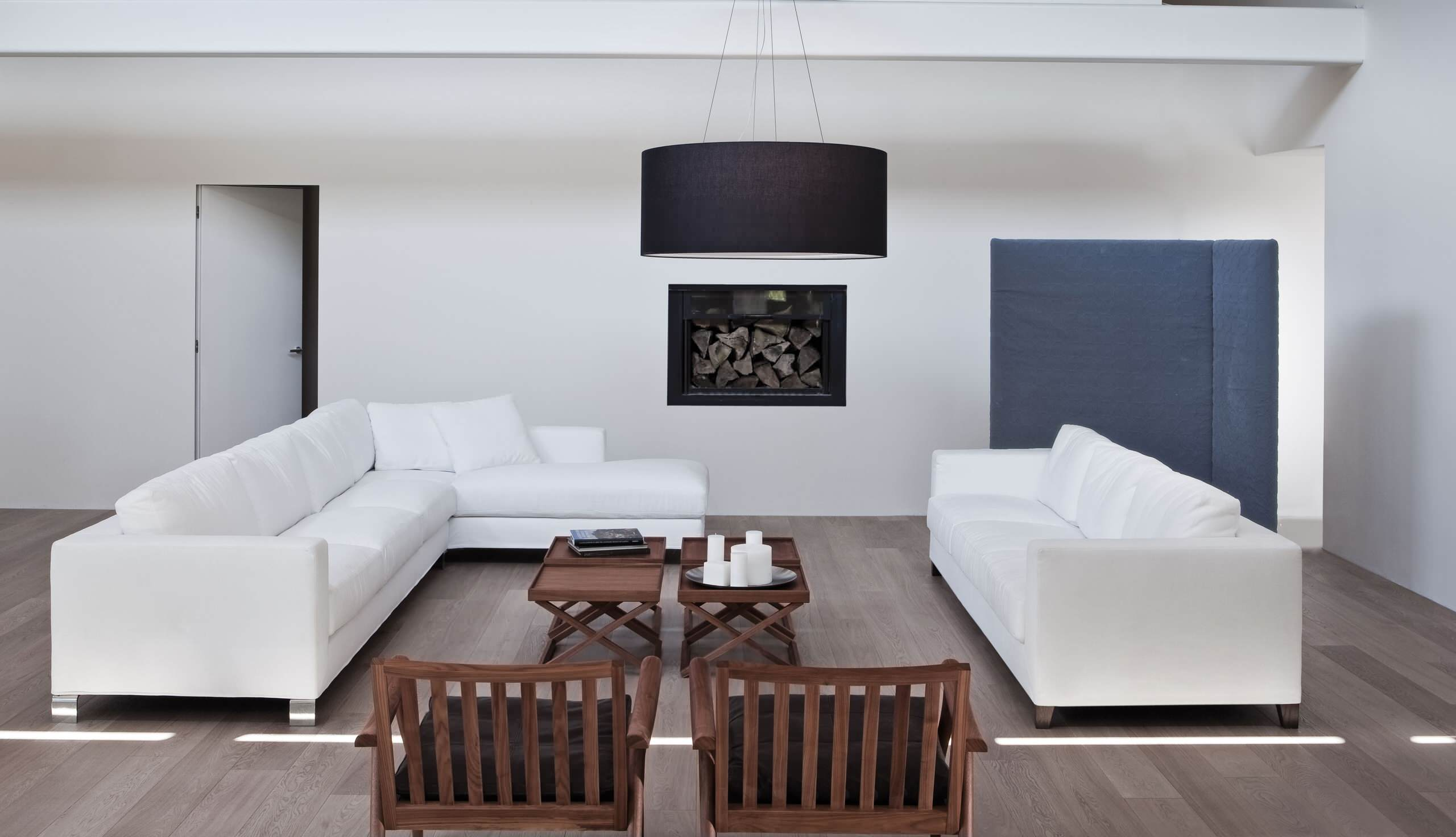 Modern Living Room With Light Wood Flooring Plus Mission Chairs And Sectional Sofa Also Drum Chandelier With White Wall Plus Wall Decor And Twin Coffee Table