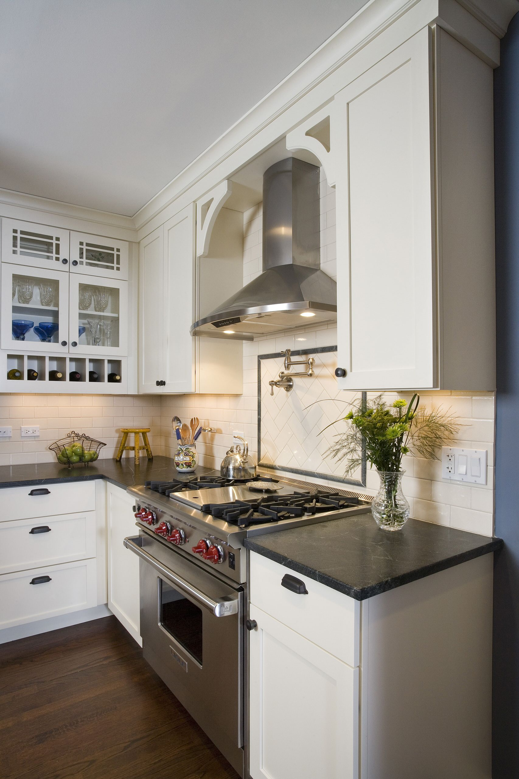 Paint Kitchen Cabinets With Pot Filler And Tile Backsplash For Traditional Kitchen Design With Switch Plate Covers And Dark Countertop Plus Gas Stove Also Dark Hardwood Floor