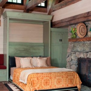 Rustic Bedroom Furniture With Wood Paneling For Wall And Murphy Bed Also Bedding And Area Rug With Wood Flooring Plus Stone Fireplace With Ceiling Beams