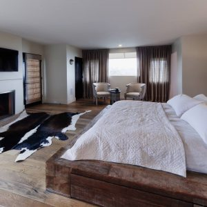 Rustic Bedroom With Cowhide Rug On Rustic Wood Flooring For Master Bedroom With Neutral Colors And Platform Bed From Reclaimed Wood Plus Tv Above Fireplace Also Window Sheers