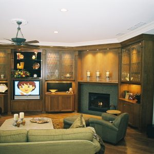 Sectional Sofa With Armchair And Dark Wood Floor For Traditional Family Room Design With Custom Entertainment Centers And Sconces Plus Fireplace Mantle Also Ceiling Fan