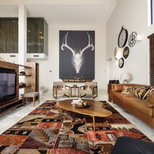 Southwestern Living Room With Marble Flooring Plus Ikat Rug And Brown Leather Sofa Also Wood Coffee Table With Large Artwork And Patchwork Also Tall Ceilings Plus Tv And Wall Clocks