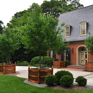 Traditional Exterior With Arched Entry And Strap Hinges Plus Black Shutters Also Brick Wall And Brick Steps With Driveway Plus Grass And Gravel In Landscape Plus Planter Boxes And Round Bushes