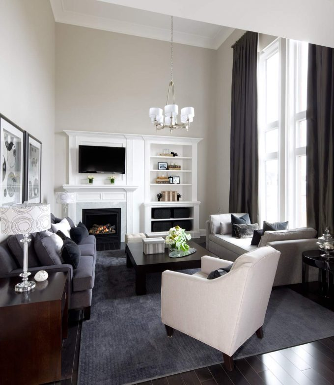 Traditional Family Room Plus Built In Bookshelves And Built In Fireplace With Chandelier Shades Also Contemporary Sofa Plus Modern Daybed On Dark Floors With High Ceilings And Tall Windows