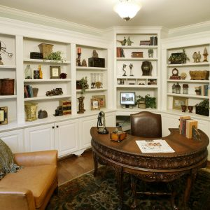 Traditional Home Office With Hardwood Flooring Plus Persian Rug And Bookshelves With Built In Cabinetry Also Ceiling Lights Plus Curved Wood Desk And Corner Shelf Unit Also Dark Hardware