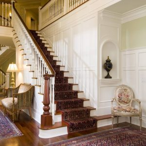 Traditional Staircase Plus Stair Carpet And Dark Stained Wood In Modern Home With Decorative Wall Panels And Hardwood Flooring Plus Persian Rug Also Railing With Spindle And Wainscot