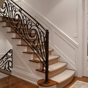 Traditional Staircase With Carpeted Staircase And Area Rug On Dark Wood Flooring Also French Doors Plus Iron Railings With Wainscoting In Modern Home Plus White Walls And Wall Decor