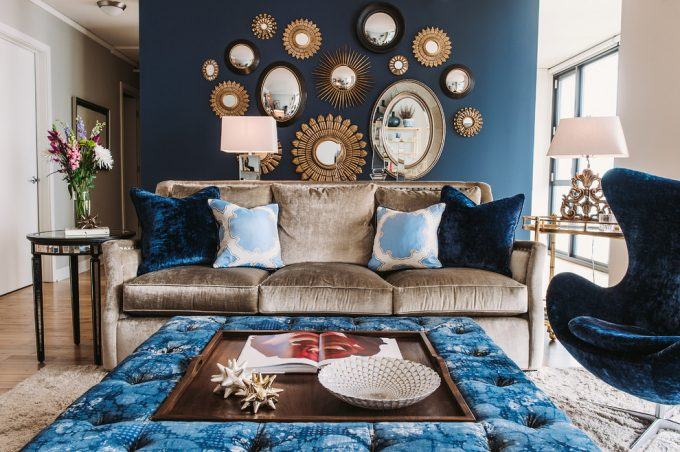 Transitional Living Room With Dark Blue Accent Wall Plus Sunburst Mirrors Also Decorative Pillows For Couches With Light Brown Sofa And Blue Egg Chair Also Custom Ottoman Plus Shag Carpet