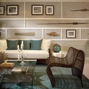 Tropical Living Room With Decorative Wall Panels Plus Wall Decor And Ceiling Lighting With Glass Coffee Table On Turquoise Rug Also Cushion On White Sofa And Woven Armchair Plus Candle
