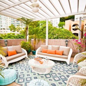 Tropical Patio Plus Ikat Rug And Flat Weave Also Garden Wall With Glass Topped Coffee Table And Lanterns Plus Leather Pouf Also Orange Seat Cushions With Tropical Plants And Woven Outdoor Furniture