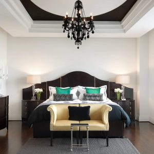 Vaulted Ceiling With Black Chandelier And Bed Linens For Contemporary Bedroom Design With Mid Century Sofa And Bombe Chest Plus Dark Hardwood Floor Also Sisal Carpet