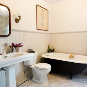 Wainscoting Bathroom With Chair Rail And Bathroom Mirror Also Wall Sconce And Pedestal Sink With Toilet And Claw Foot Tub Plus Penny Tile Flooring With Indoor Plants