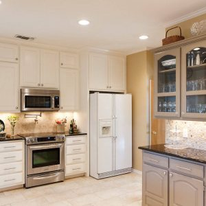 White Kitchen Cabinets With Under Cabinet Microwave And Under Cabinet Lighting In Traditional Kitchen With Mosaic Tile Blacksplash And Pot Filler Plus Electric Stove Also Laminate Tile Flooring