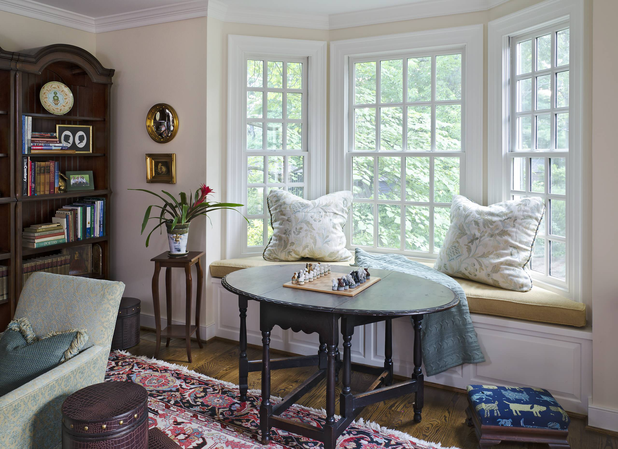 Exciting Bay Window Seat for Interior Home Design: Wood Flooring With Feizy Rug And Dark Oval Table For Traditional Family Room Design With Bay Window Seat And Decorative Cushions Plus Armchair Also Creative Bookshelves
