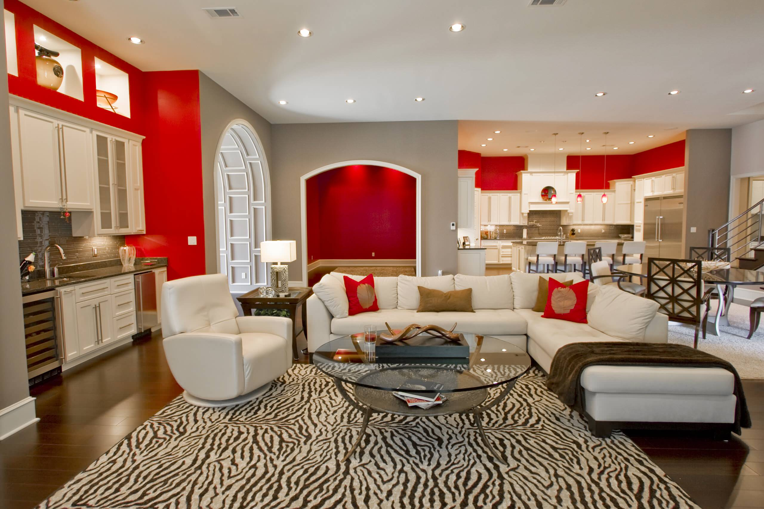Home Interior Decor with Stunning Zebra Rug: Zebra Rug With Best Sectional Sofa And Gold Throw Pillow Also Round Glass Coffee Table Plus Gray Wall And White Kitchen Cabinets Also Ceiling Lighting For Modern Living Room