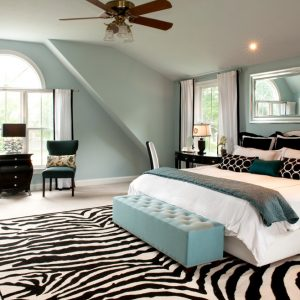 Zebra Rug With Modern Ceiling Fan And Recessed Lighting Also Arched Window Plus Light Blue Bench And Rectangular Mirror Also White Baseboards For Modern Bedroom Design