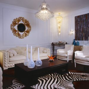 Zebra Rug With Modern Crystal Chandelier And Modern Coffee Table Also Sunburst Mirror Plus Wooden Flooring And White Walls Also White Sofa For Modern Living Room