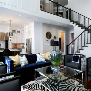 Zebra Rug With Side Tables And Staircase Ideas Also Glass Coffee Table Plus Ceiling Lighting And Black Sofa Also Dark Wooden Floor For Modern Living Room Design Ideas