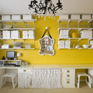 Accent Wall And Crystal Chandelier In Craft Room Plus Organization And Stools Also Storage Boxes For Studio With Wall Shelves And Work Station Plus Yellow Walls Also Small Table Lamp