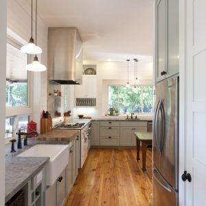Apron Sink And Butcher Block Also Farmhouse Table With Gray Countertop In Farmhouse Kitchen Plus Green Cabinets And Kitchen Shelves Also Pendant Lighting With Wood Flooring