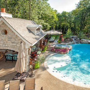 Aquatic And Backyard Retreat With Boulders Plus Covered Patio Also Curved Pool With Pool House Designs Plus Flowers And Fountain Also Outdoor Dining And Outdoor Living Space