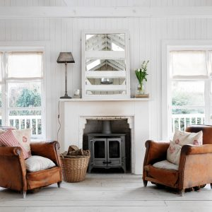 Basket And Brown Leather Armchair For Living Room Furniture In Coastal House Plus Firplace And Floral Cushions Also Mirror With Table Lamp On White Fireplace Mantle And Armchair On Wooden Floor