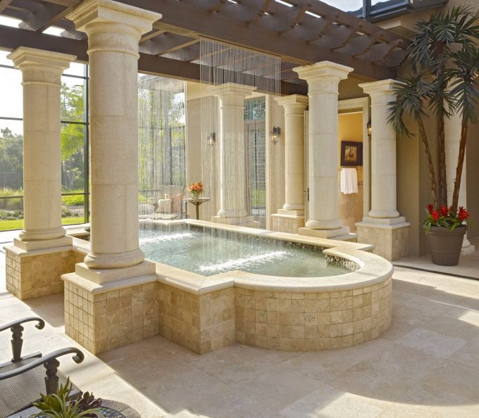 Beige Stone Patio With Beige Stucco Exterior Plus Ceiling Water Feature And Elevated Pool With Pillar Also Indoor Fountains Plus Red Flowers And Window Wall With Wood Trellis