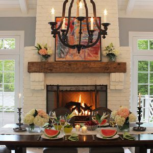 Black Chandelier In Traditional Dining Room With Candleholder On Small Dining Table Plus Exposed Beams Also Fireplace And Mantel With Gray Walls Plus Sconce And Transom Window