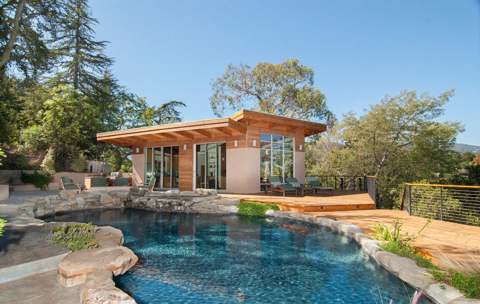 Inspiring Pool House Designs in Your Home: Cable Railing For Contemporary Pool With Pool House Designs And Organic Pool Shape Plus Outdoor Chaise Lounge And Outdoor Furniture Also Outdoor Lighting With Rock Wall And Views