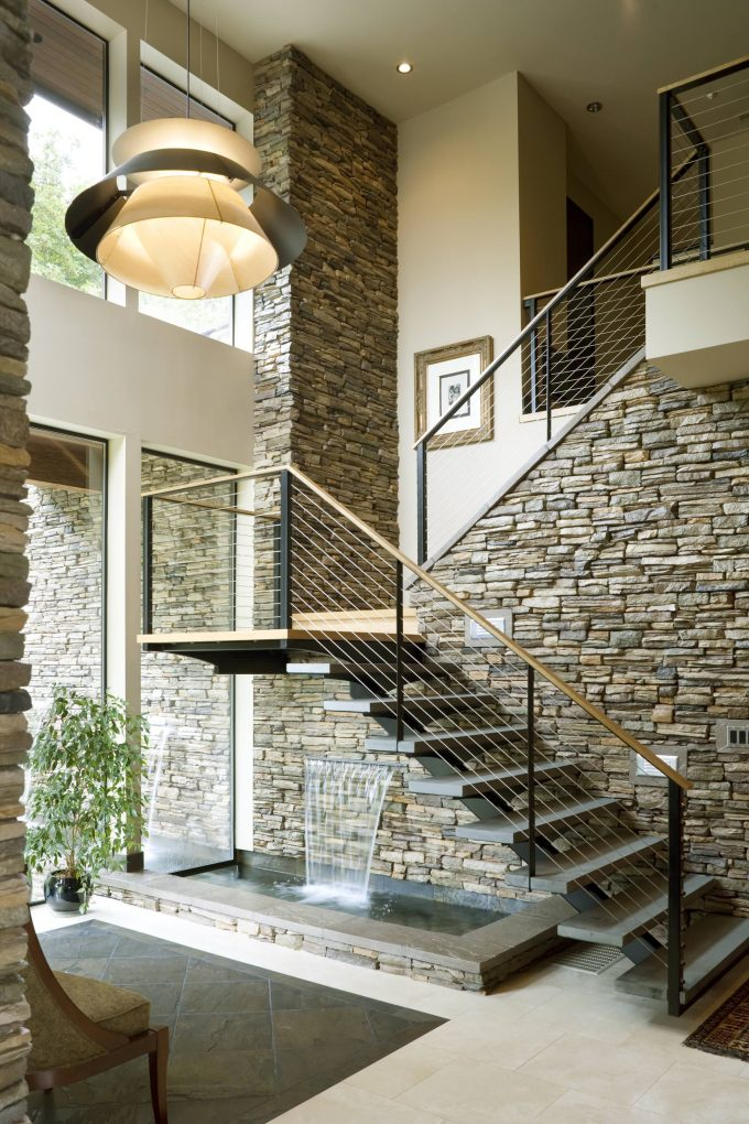 Cable Railing With Open Staircase And Open Tread Plus Pendant Light Also Stacked Stone With Tall Windows And Tile Flooring Plus Indoor Fountains And Houseplant