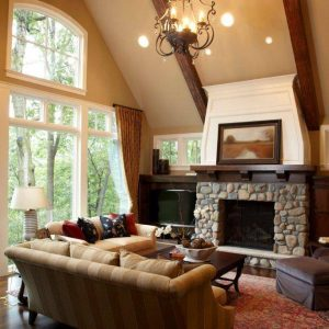 Ceiling Lighting And Classic Chandelier In Traditional Living Room With Dark Wood Flooring And Decorative Pillows For Couches On Sofas Plus Oriental Rug And Stone Fireplace With Mantel
