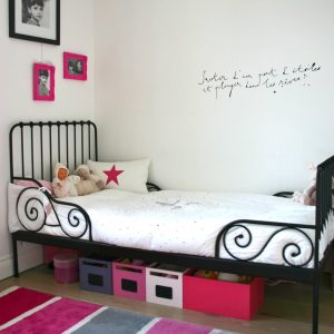 Colorful Area Rug Also Frames On White Wall For Girls Room Plus Hot Pink With Iron Bed Plus Toy Storage And Storage Boxes Also Underbed Storage With Writing On The Wall And Wood Flooring