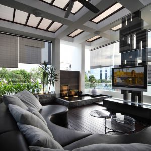 Contemporary Family Room Plus Black Leather Couch And Black Roller Shades Also Indoor Fountains With Kalwall Ceiling And Skylights Plus Wall Mounted Tv Also Glass Coffee Table