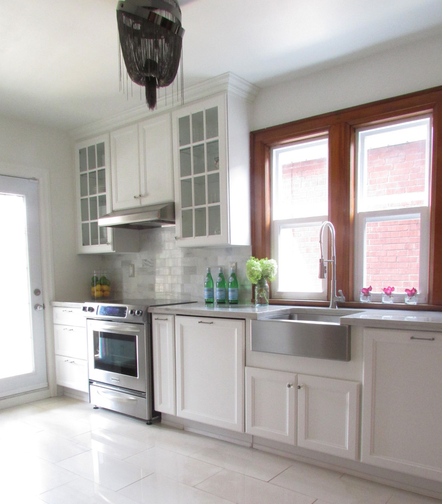 Crown Point Cabinetry And Glass Panel Cabinets With Gray Counter Also Apron Sink Plus Natural Lighting And White Tile Floor With White Walls And Wood Window Frame