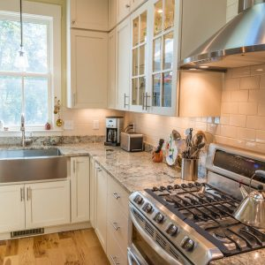 Farmhouse Kitchen With Double Hung Window And Glass Front Cabinets Also Stainless Steel Hood Plus Apron Sink With Subway Tile Backsplash And Cabinet Under Lighting