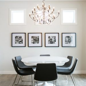 Modern Dining Room With Beige Wall Plus Photo Collage Ideas And Black Dining Chair Also White Round Dining Table With Contemporary Chandelier And Light Wood Floor Also Natural Lighting