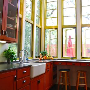 Southwestern Kitchen Plus Apron Sink With Black Countertop Also Drawer Pulls And Glass Front Cabinets With Open Shelving And Tall Windows Also Bar Stools On Black Tile Flooring