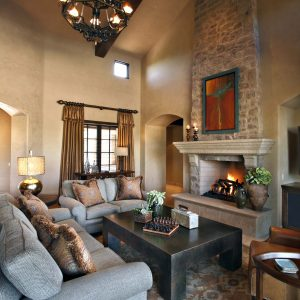 Traditional Living Room With Arch Doorway And Beige Wall Also Brown Area Rug With Brown Leather Armchair Plus Brown Throw Pillows And Dark Coffee Table Also Mantel For Stone Fireplace